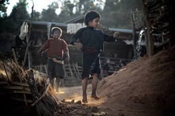 Two boys in evening light  running on a dusty path in an  Eng (Ann)  village near Kyaing Tong (Kentung), Shan State, Myanmar (Burma)