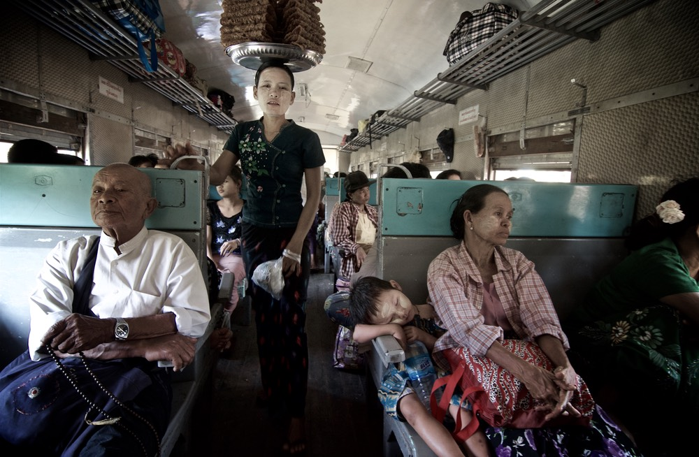 Vernod balancing food on her head and passengers in a train, Myanmar (Burma), Asia